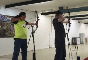Two archers line up using tripods to assist in aiming their shots.