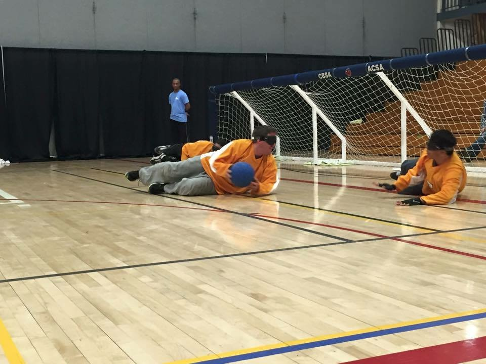 Athletes in yellow jerseys playing goalball. Three players lay on the court with a net spanning the width of the court behind them. the player in the centre is about to pass to the player on his left side.