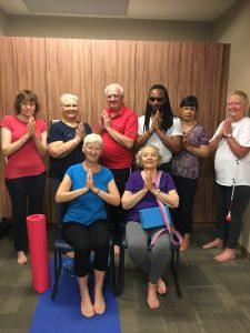 7 of our 2017-2018 season yoga participants pose for a photo, many with hands folded and yoga mats present!