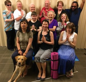 12 of our 2017-2018 season yoga participants pose for a photo, many with hands folded. A yellow lab guide dog sits to the front left, and a pink yoga mat is rolled standing in the centre.